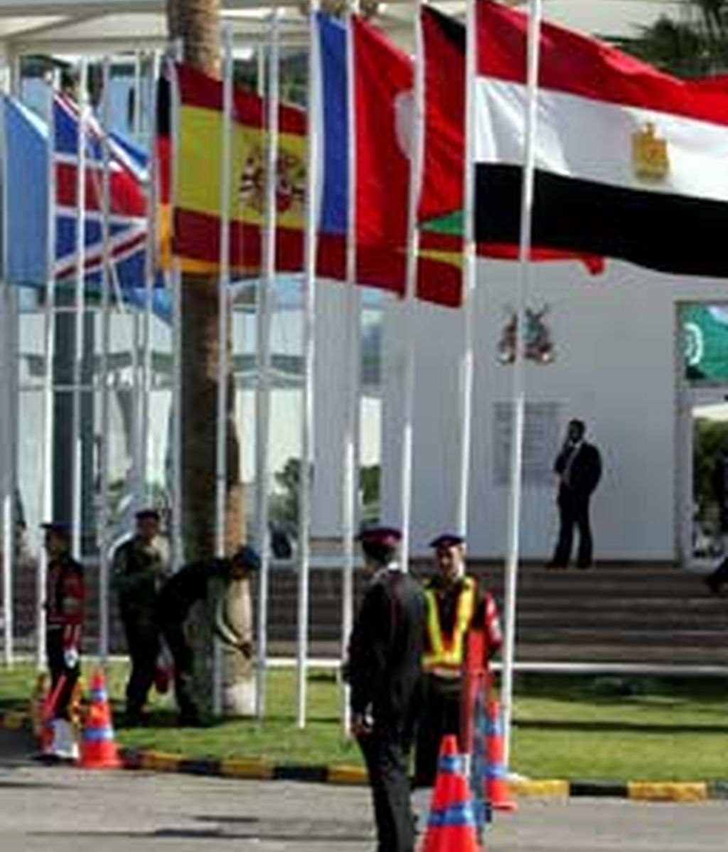 Varios soldados egipcios vigilan junto a las banderas de los países que participan en una cumbre internacional que busca sumar esfuerzos en favor de la reconstrucción de Gaza. Foto: EFE