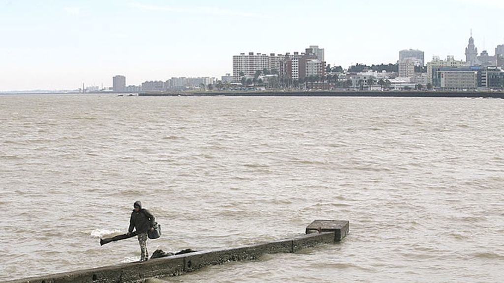 Un pescador camina junto al espectacular paisaje de la capital uruguaya, Montevideo