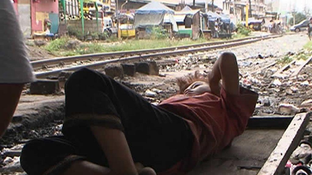 Una mujer durmiendo en las vias del tren