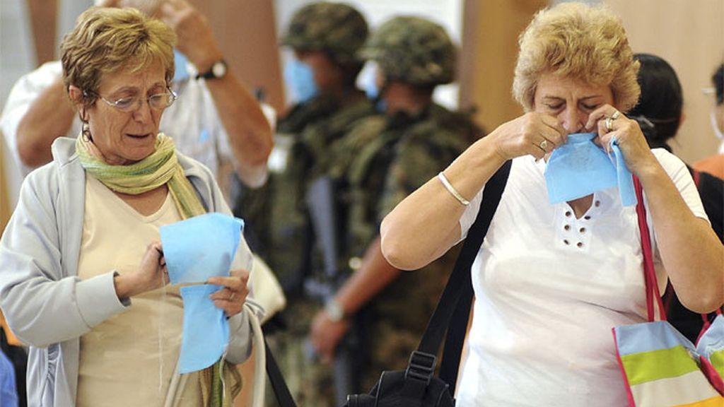 Mujeres poniéndose una mascarilla en un aeropuerto