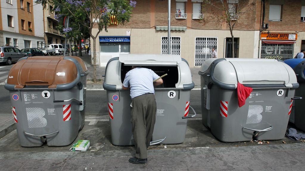 Un hombre busca en la basura