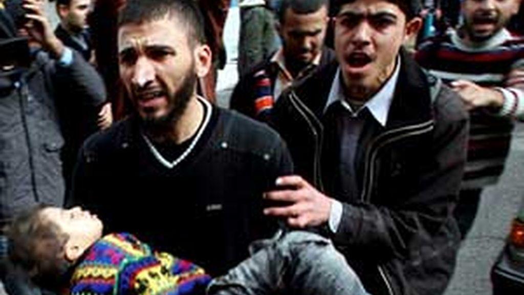 Un padre lleva en brazos a su hijo herido en el bombardeo. Foto: EFE