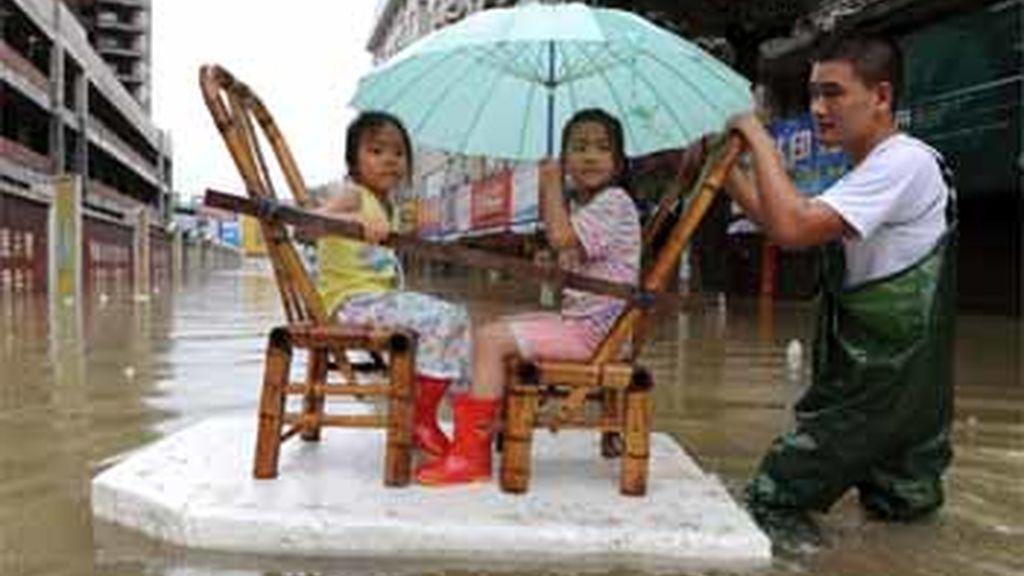 Un hombre tira de una balsa improvisada para transportar a dos niñas tras el tifón 'Morakot', en China