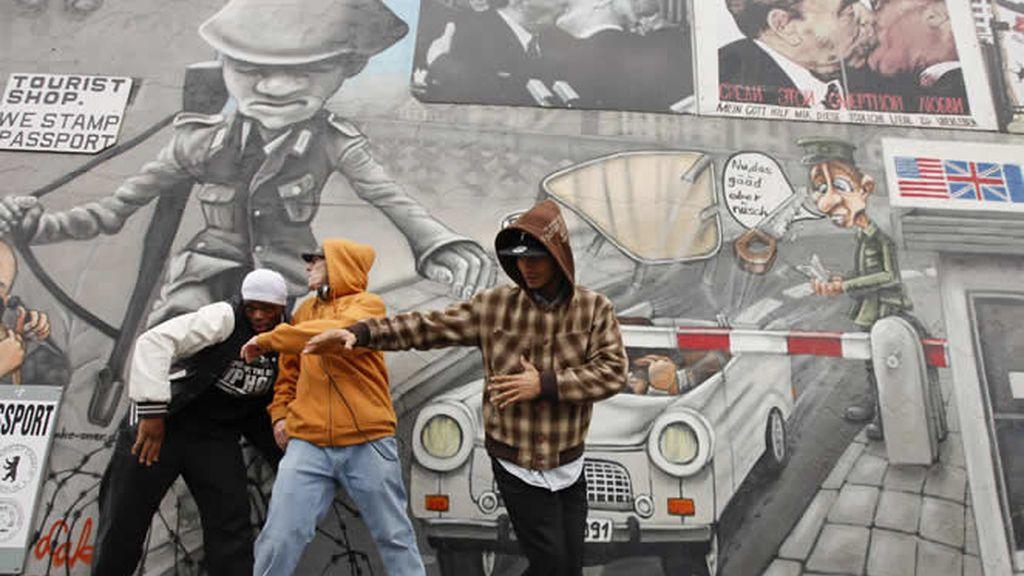 Baile callejero frente a pinturas políticas en el muro