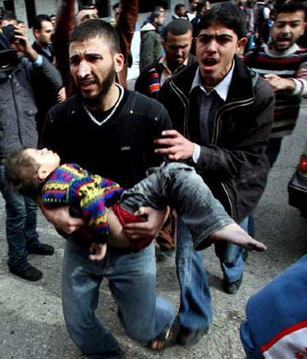 Un palestino lleva en brazos a su hijo herido tras el bombardeo de Israel a Gaza. Foto: EFE