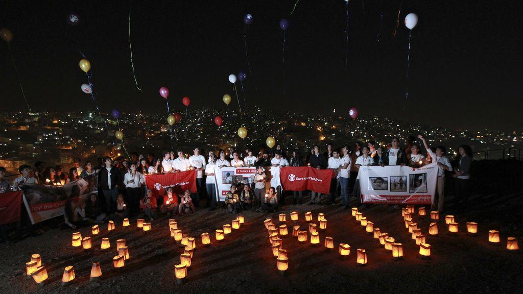 Varios niños ponen con velas el nombre de Siria en el segundo aniversario del comienzo de la guerra