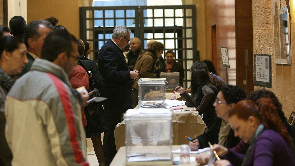 Varias personas acuden a las urnas para votar en un colegio electoral en Tarragona