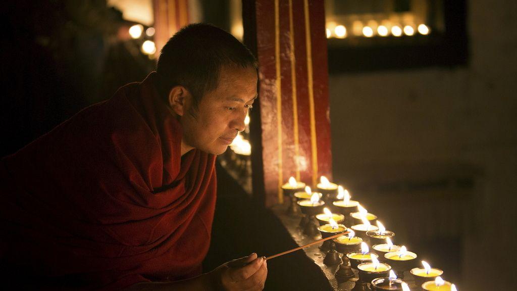 Un monje tibetano enciende una lámpara en el templo de Lhasa