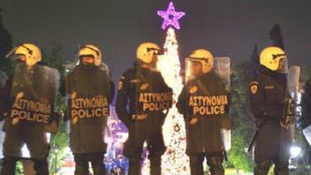Oficiales de policía resguardan la calle junto a un árbol de Navidad en la plaza principal de Atenas. Foto: EFE