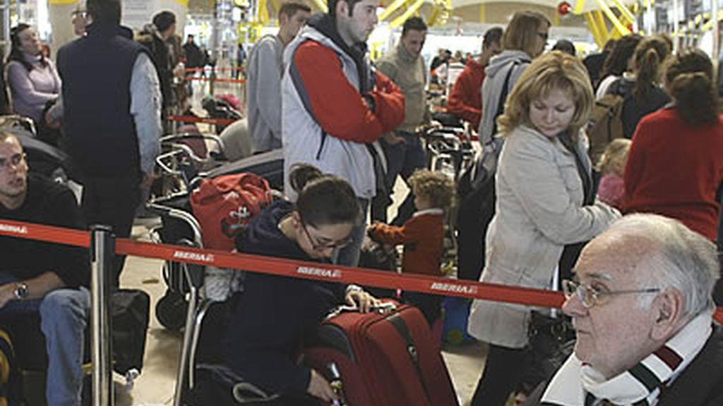 Un grupo de frustrados viajeros espera una larga cola en el madrileño aeropuerto de Barajas