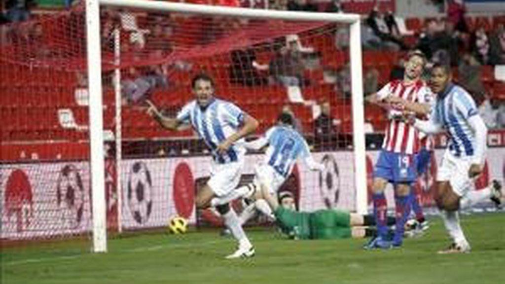 El defensa brasileño del Málaga, Weligton Robson (i), celebra ante el centrocampista uruguayo del Sporting, Sebastián Eguren (c), el gol conseguido por Robson, el primero para el conjunto durante el partido correspondiente a la decimo séptima jornada de la Liga en Primera División que ambos equipos jugaron en el estadio asturiano de El Molinón. EFE