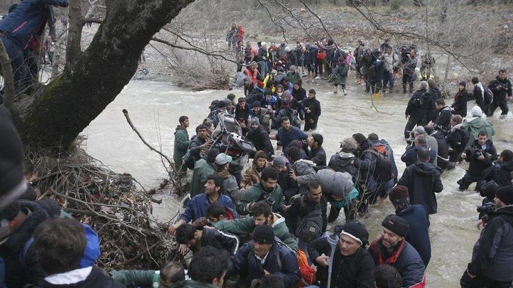 Un grupo de refugiados cruza un río cerca del campamento de Idomeni para intentar entrar en Macedonia