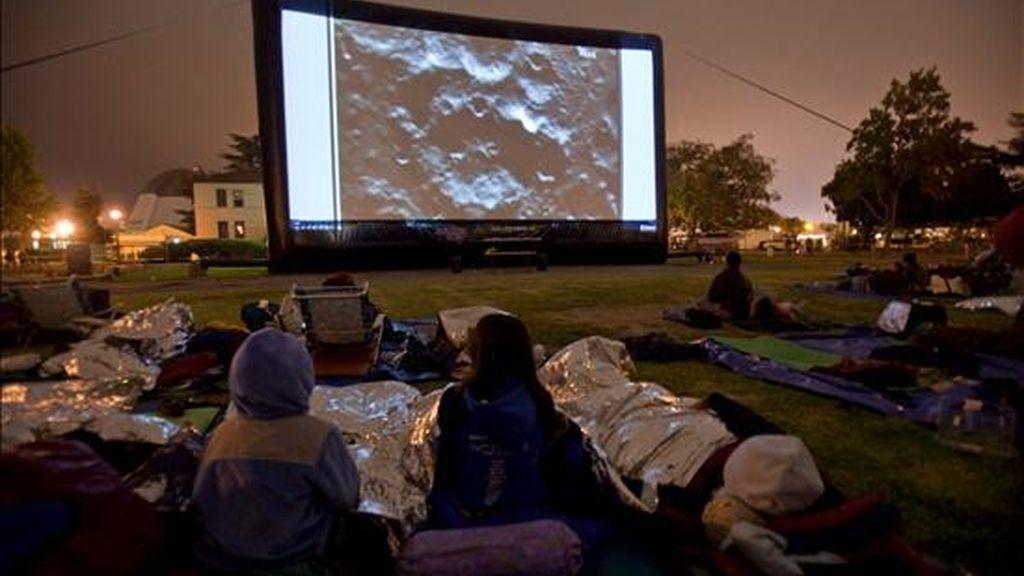Varios aficionados a la astronomía observan la transmisión en vivo del doble impacto de la sonda LCROSS de la NASA y su cohete Centauro en el fondo del cráter Cabeus en el polo sur de la Luna. EFE