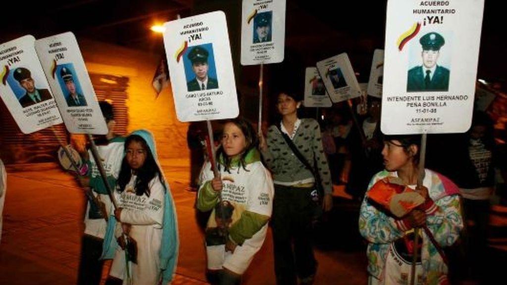 Un grupo de niños camina con carteles con las fotos de sus familiares secuestrados por las FARC por una céntrica vía de Bogotá, después de que la guerrilla anunciara la decisión de liberar a seis rehenes. FOTO: EFE.