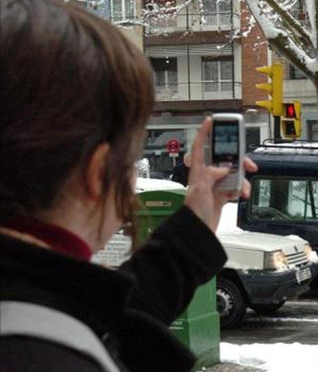 Una joven fotografía con su teléfono móvil. EFE/Archivo