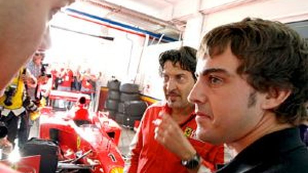 Fernando Alonso atiende a las explicaciones de un técnico de la escudería Ferrari sobre uno de los monoplazas. Foto: EFE