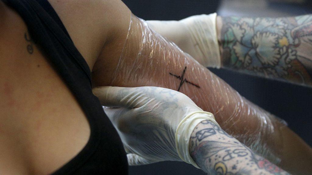 Un tatuador tatúa el brazo a una mujer