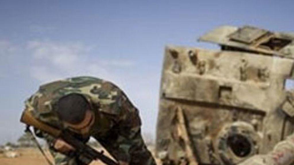 Un soldado rebelde examinan un tanque destruido de las fuerzas gadafistas