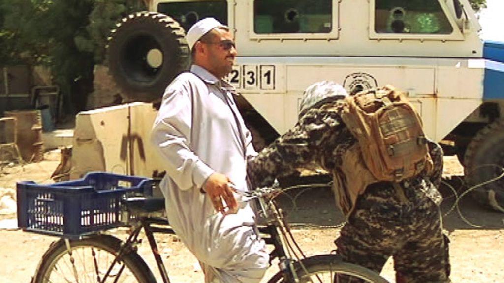 Un militar examina minuciosamente a un civil durante un control