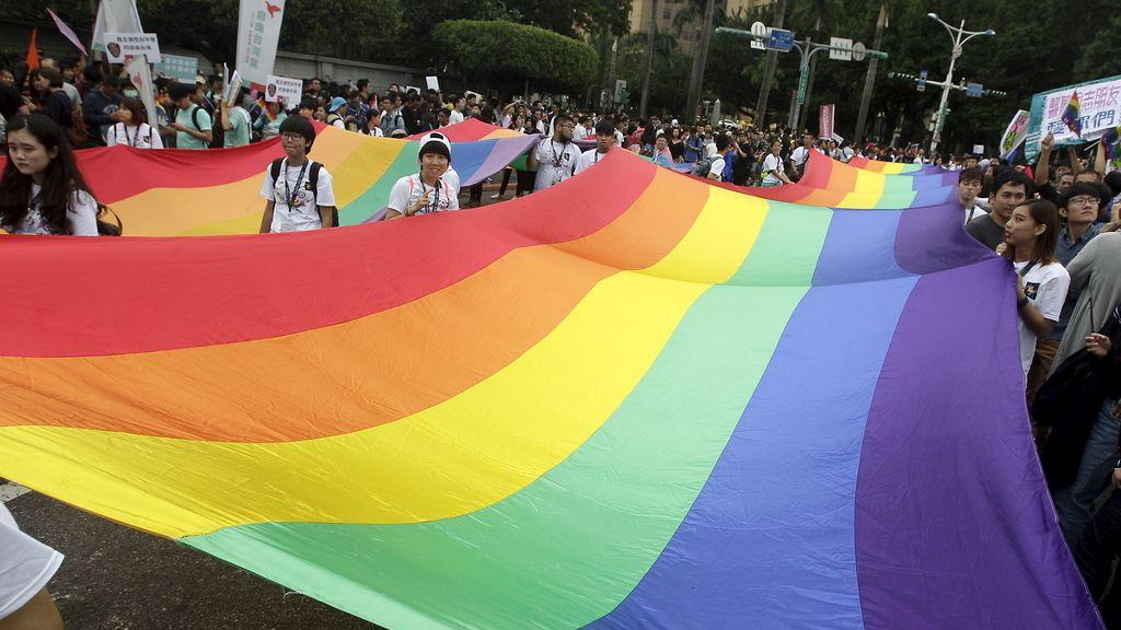 Manifestantes sujetan una bandera gay