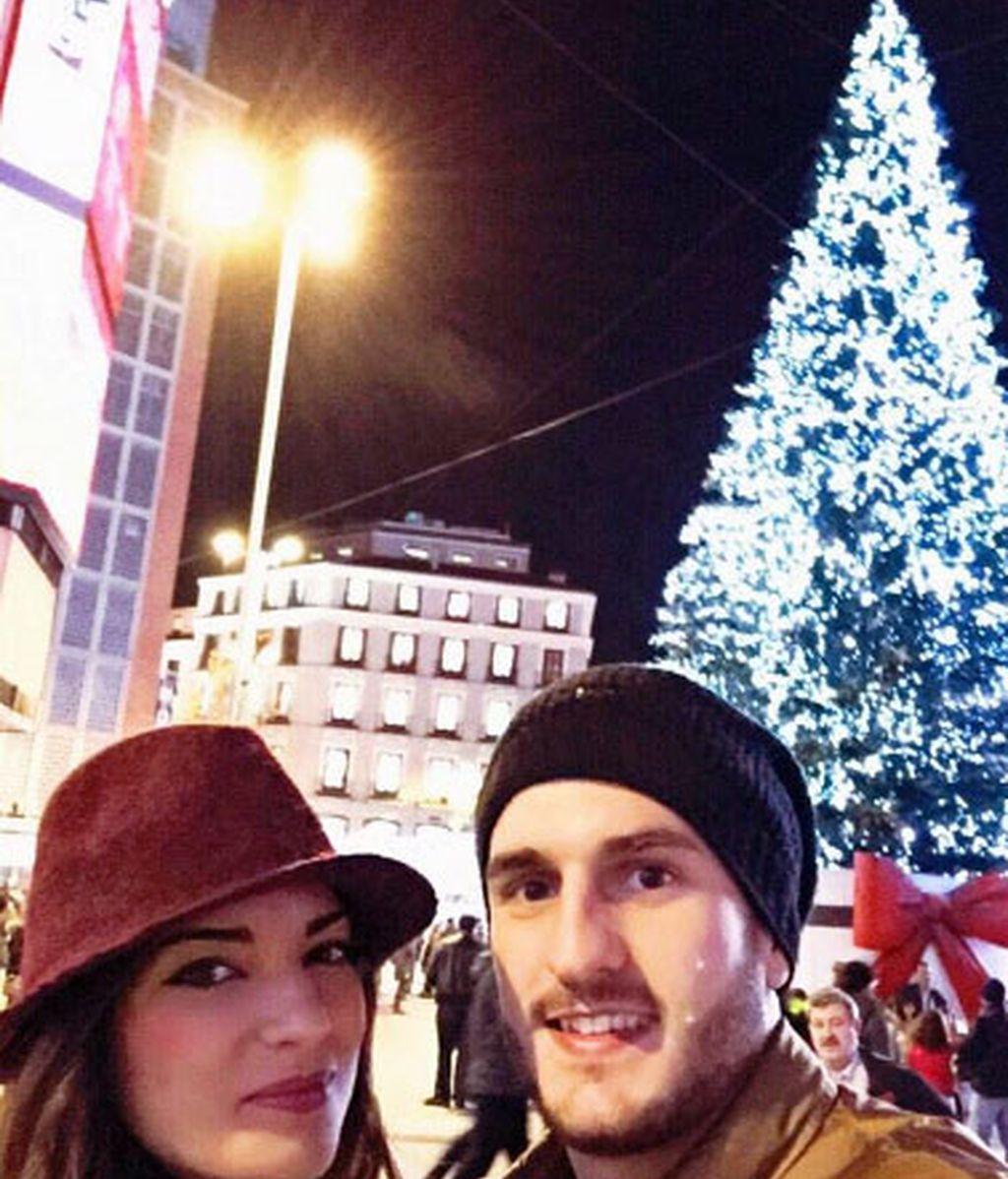 Koke, junto a su novia, en el árbol de la Plaza de Sol de Madrid