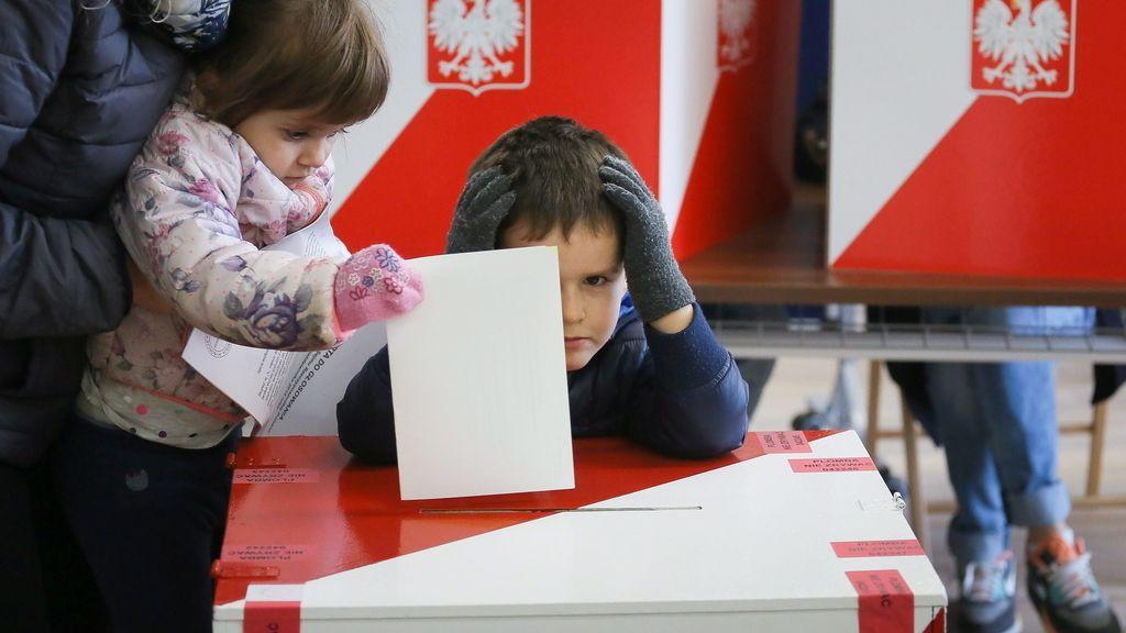 Una mujer vota junto a sus hijos en Varsovia