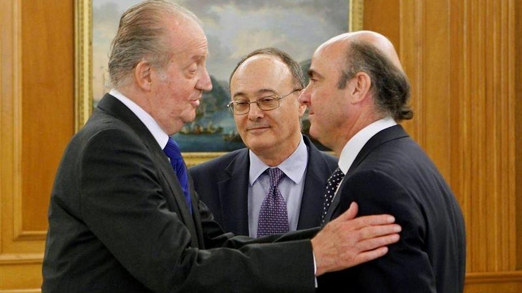 El rey Juan Carlos conversa con el ministro de Economía, Luis de Guindos (d), en presencia del nuevo gobernador del Banco de España, Luis María Linde de Castro (c), momentos antes de que éste prometiera hoy ante el rey su cargo al frente de esta institución, en una breve ceremonia celebrada en el Palacio de la Zarzuela.