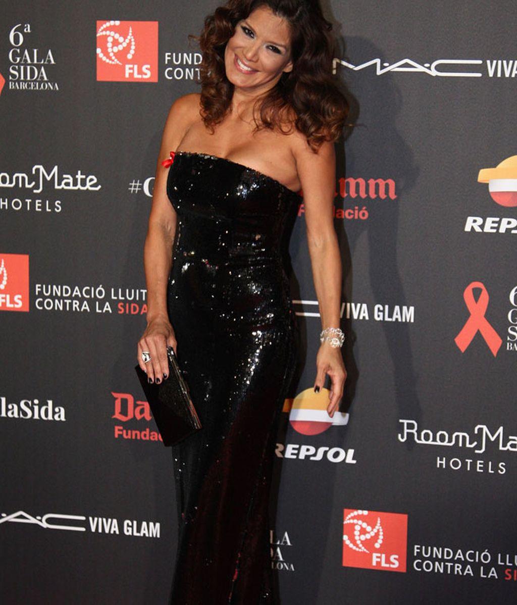 Ivonne Reyes, con brillo negro largo, pelo suelto y el lacito rojo.