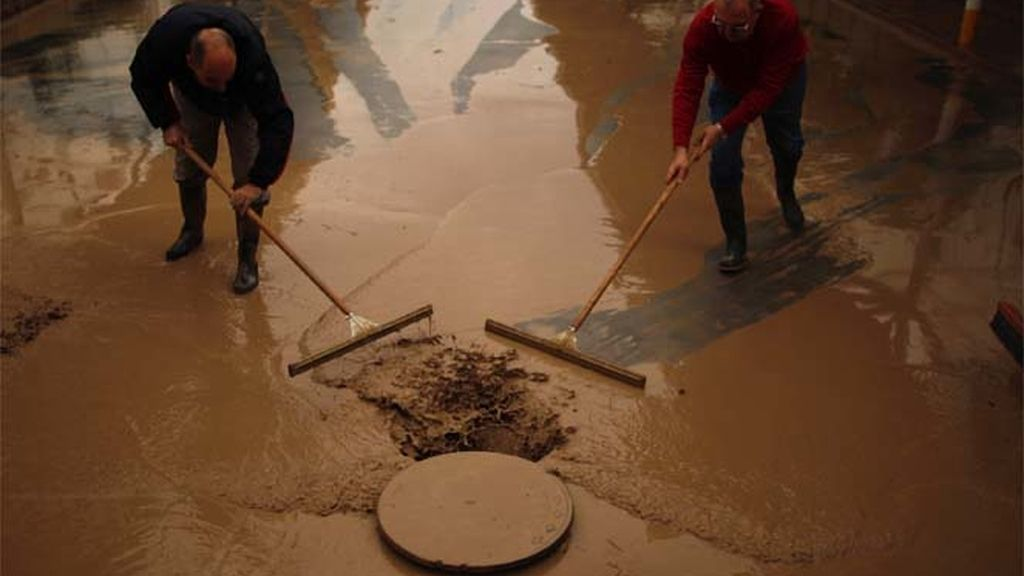 Vecinos de Écija colaboran para limpiar el lodo de las calles