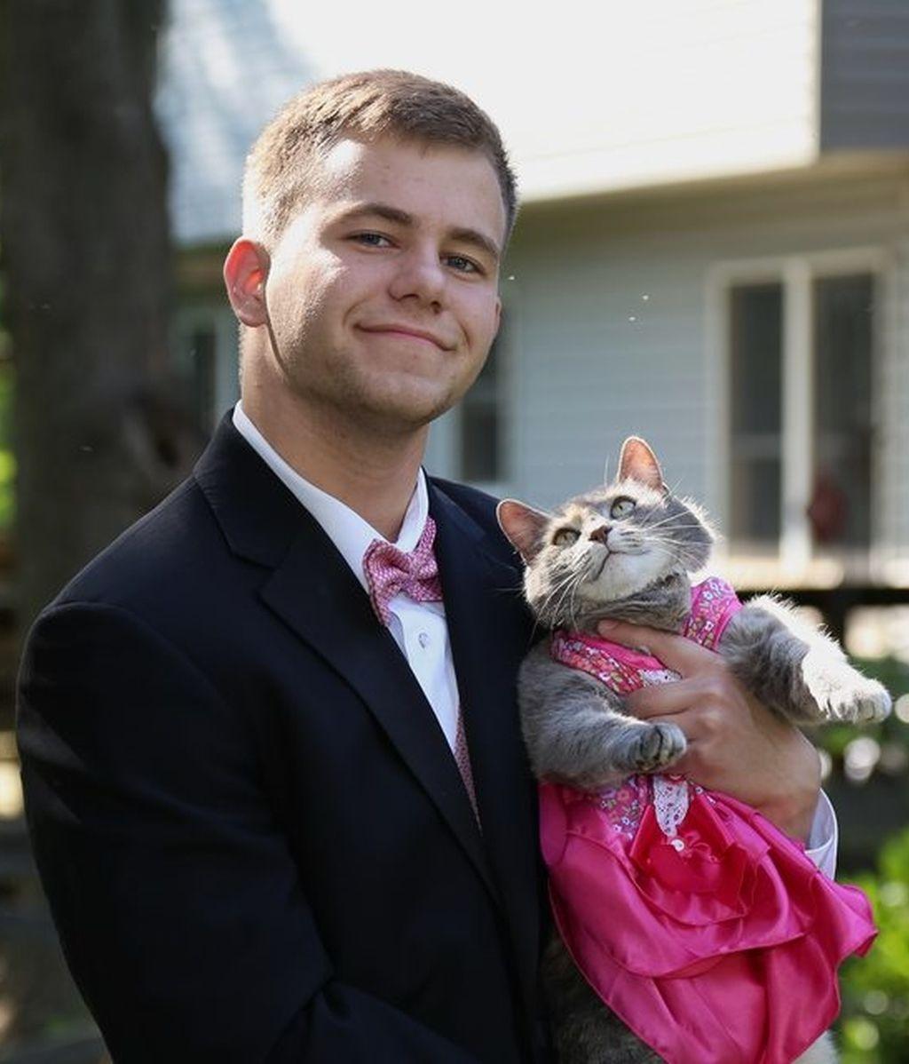 Un joven va con su gato a la graduación