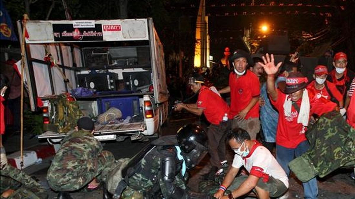 """Soldados tailandeses heridos son ayudados por miembros de los llamados """"camisas rojas"""" durante los enfrentamientos ocurridos hoy en Bangkok, entre las fuerzas de seguridad y los manifestantes que persiguen la caída del Gobierno de Tailandia. EFE"""