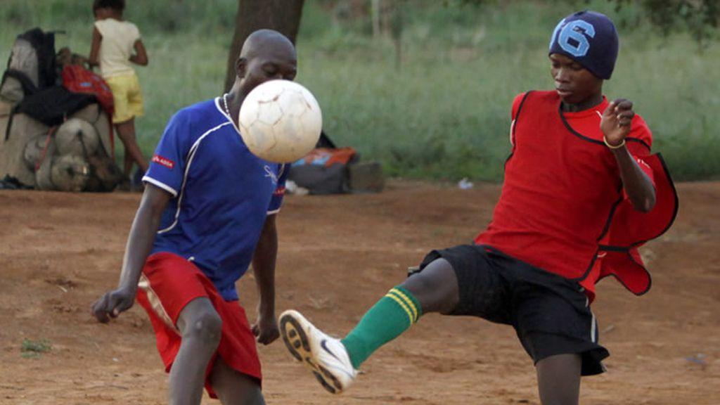 Dos jóvenes juegan al fútbol en la calle