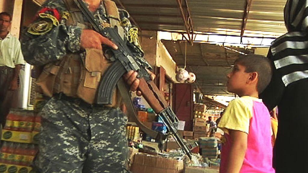 Un niño irakí mira atentamente a un miembro de las fuerzas de seguridad