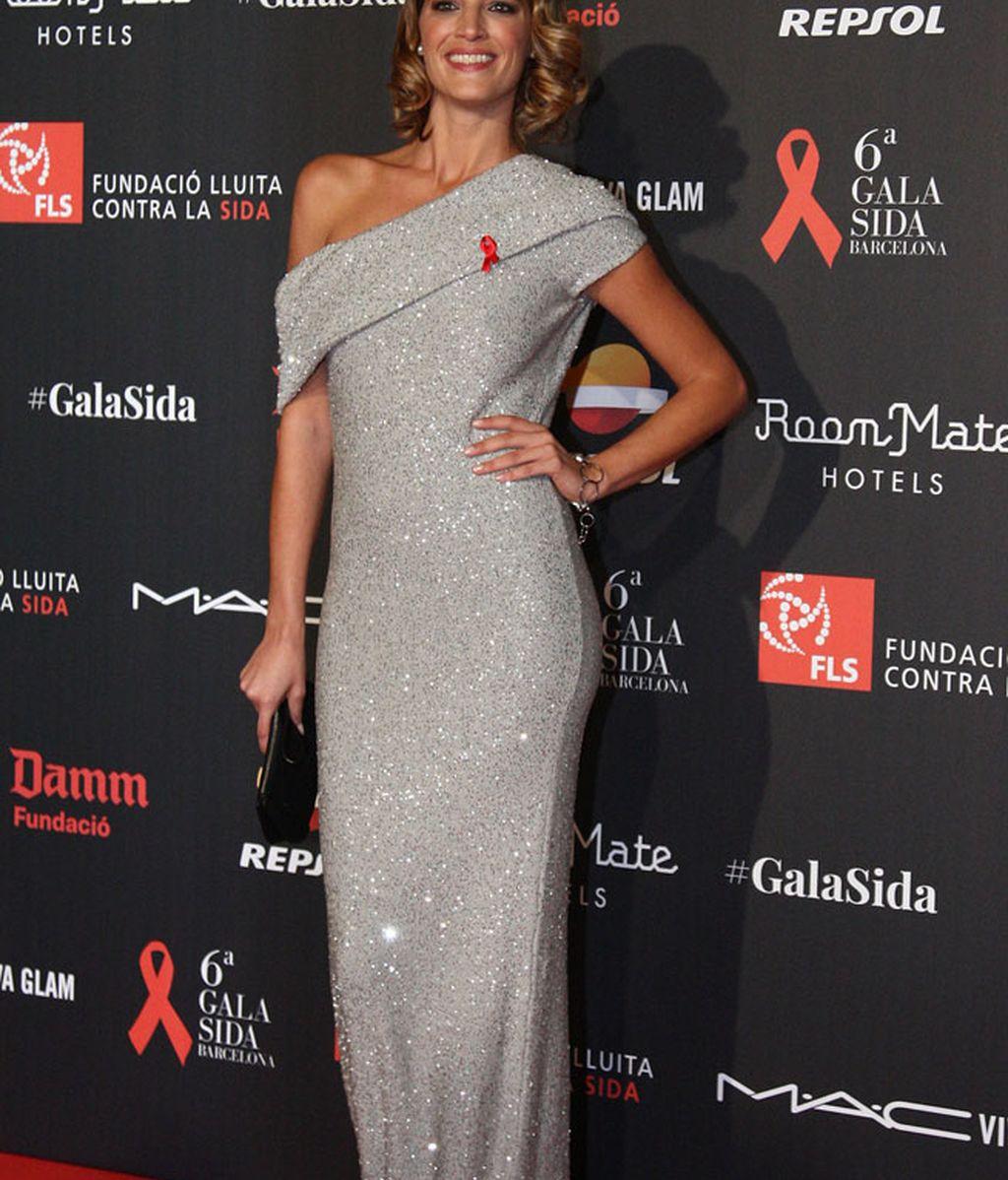 Laura Sánchez con vestido de brillo gris largo y hombro al aire