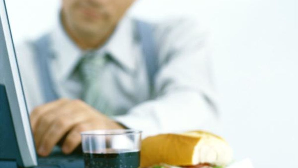 Un hombre comiendo mientras trabaja