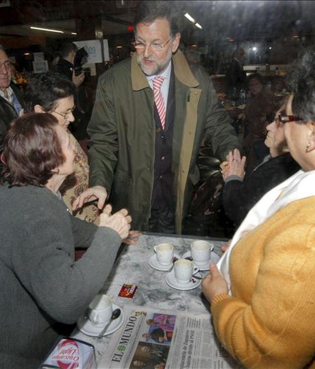 El presidente del PP, Mariano Rajoy, saluda a varias mujeres en una cafetería de la localidad coruñesa de Rianxo, antes de participar en varios actos preelectorales de su partido. EFE