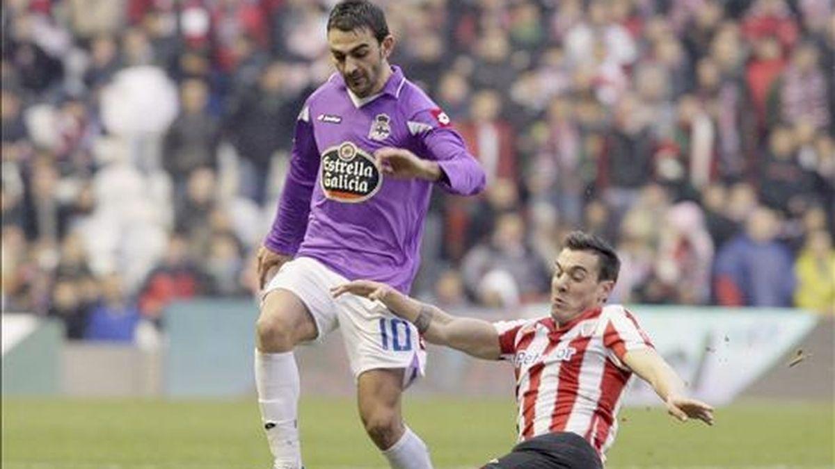 El delantero del Deportivo Adrián López (i) desborda al defensa del Athletic Club de Bilbao Xabier Castillo durante el partido correspondiente a la decimoséptima jornada de Liga en el estadio San Mamés. EFE