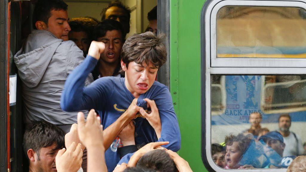 Los inmigrantes pelean por poder subir a un tren en la estación de Budapest