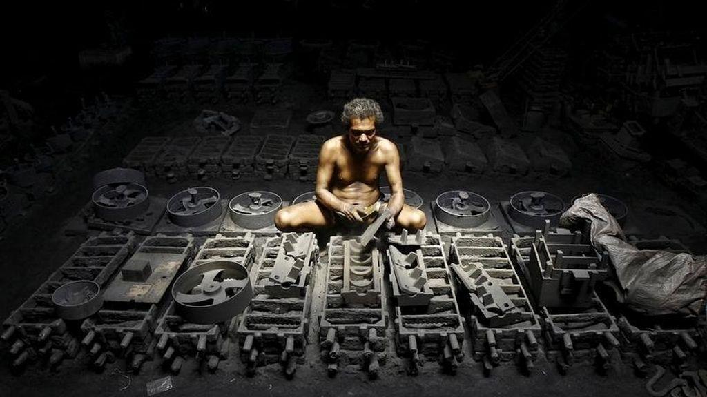 Un trabajador de una fábrica de hierro en India