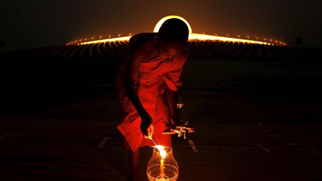Monje budista enciende una vela en el Makha Bucha