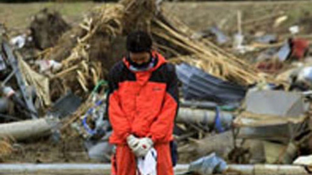 Un bombero guarda un minuto de silencio un mes después del seísmo que terremoto y posterior tsunami que arrasó la costa nororiental japonesa.