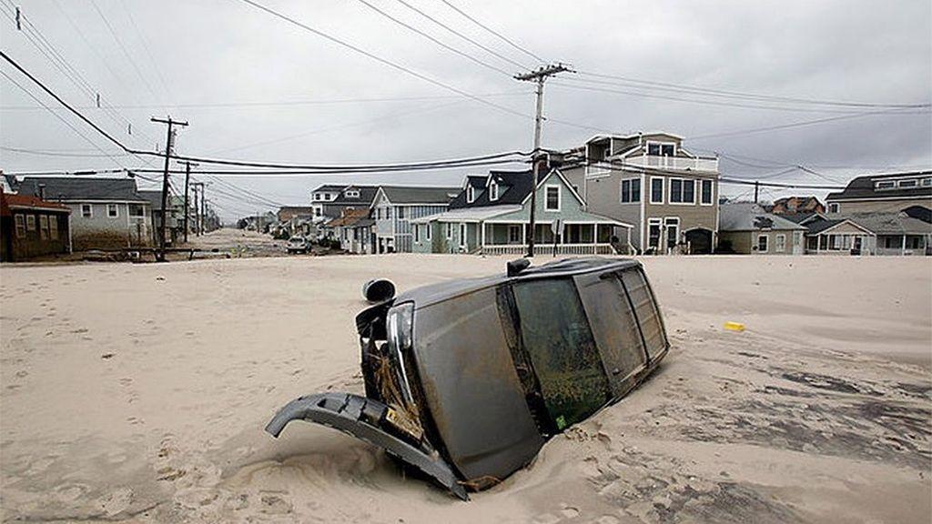 Un coche aparece en medio de una playa de Nueva ersey tras el paso de Sandy