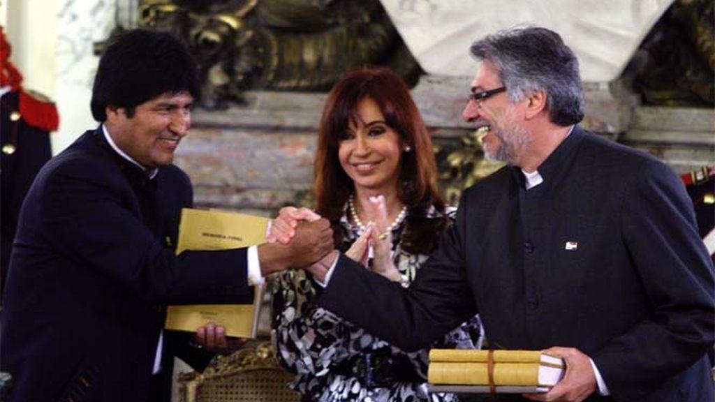 Evo Morales y Fernando Lugo se dan la mano tras firmar el acuerdo lomítrofe ante la presidentra de Argentina.