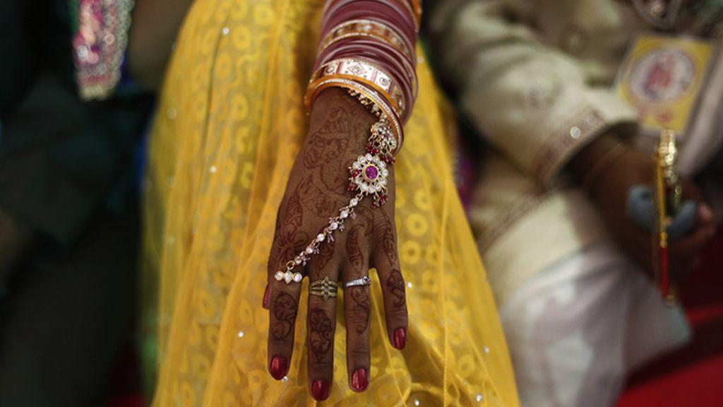 Una mujer india en una boda con las manos pintadas con hena