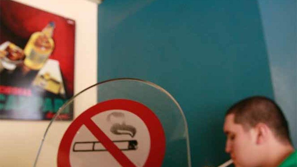 Un fumador se enciende un cigarro en un café de Atenas