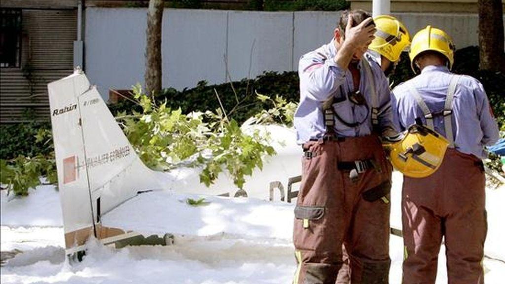 Un grupo de bomberos conversa en el casco urbano de la localidad de Badia del Vallés junto a los restos de una avioneta siniestrada en 2005. EFE/Archivo