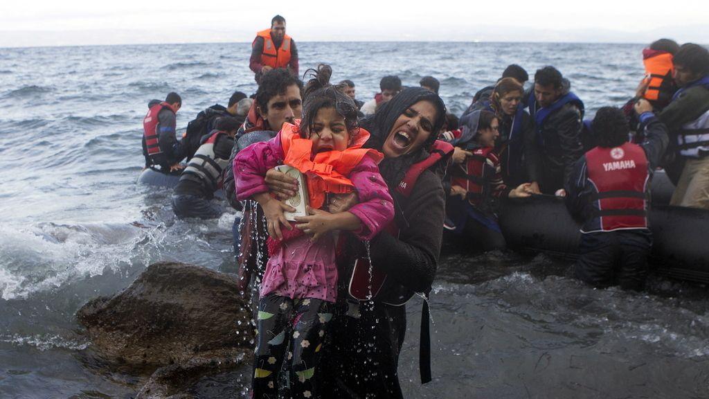 Una refugiada siria saca a una niña del mar