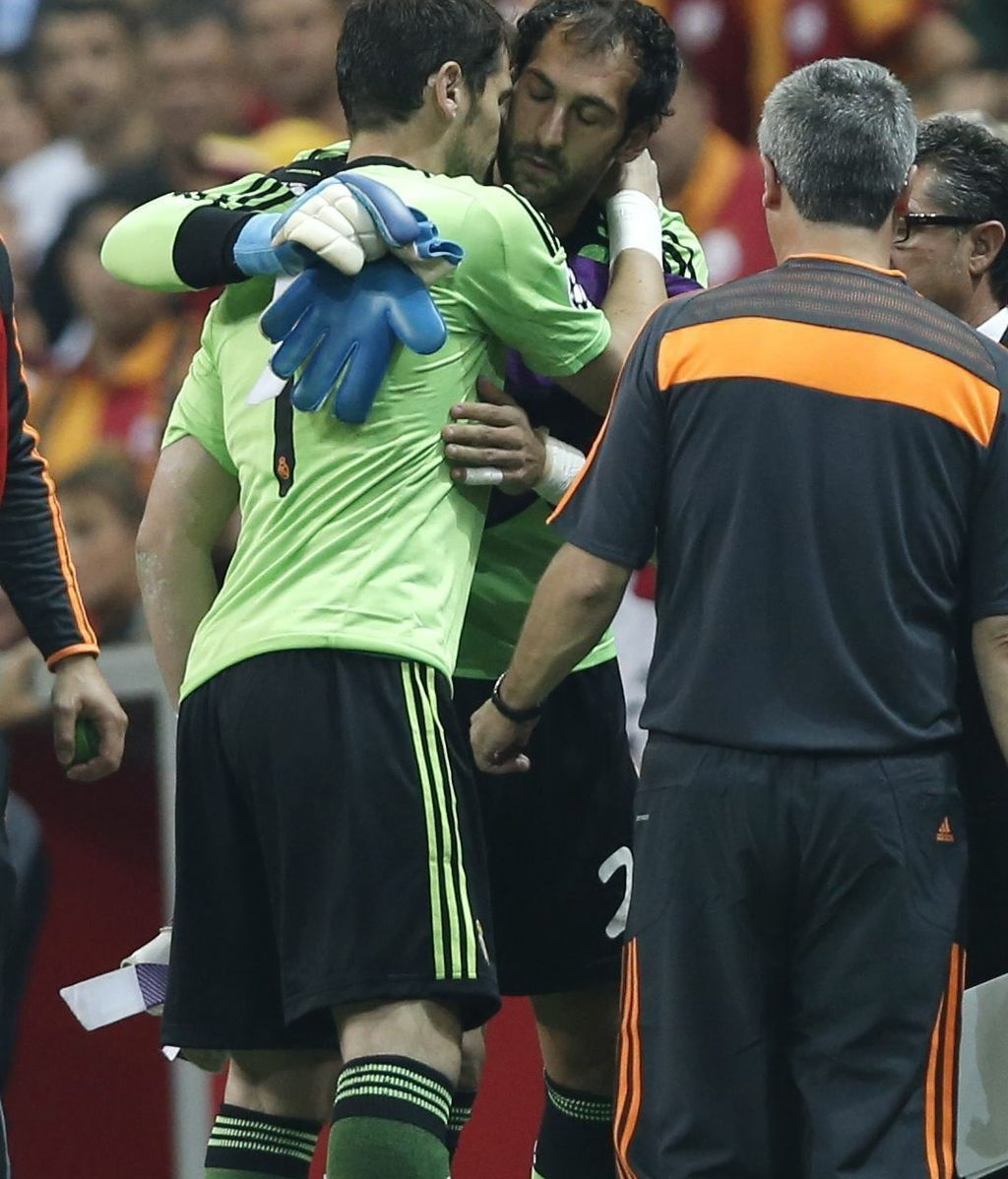 El guardameta del Real Madrid, Iker Casillas (izda), recibe el abrazo de su compañero Diego López (c), tras retirarse lesionado del primer partido del grupo B de la Liga de Campeones disputado frente al Galatasaray
