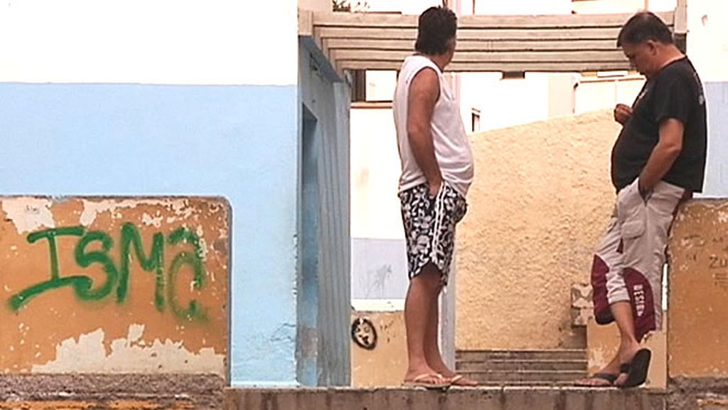 Dos hombres esperan pacientemente en una calle del barrio