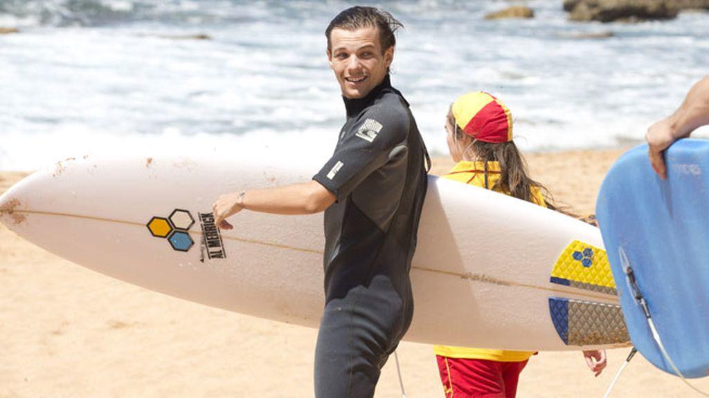 Liam y Louis se han subido a una tabla de surf, vestidos con un traje de neopreno